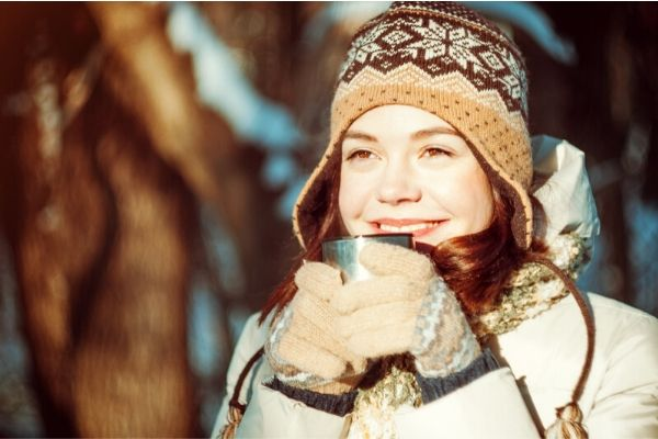 girl in a cold climate drinking a warm fluid